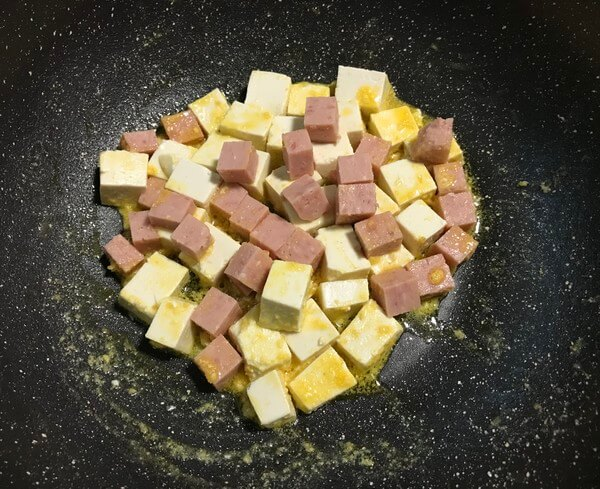 Pour in tofu, luncheon meat, and push gently with a spoon to avoid tofu cracking