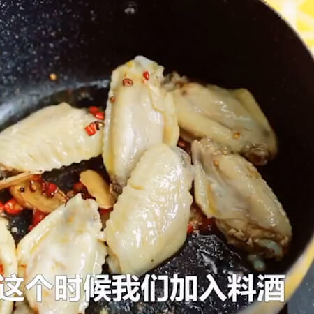 Add chicken wings, cooking wine, soy sauce, soy sauce, rock sugar, stir fry until colored.