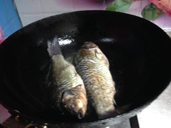 Heat a little oil in the pot, put the carp on low heat and fry until golden on both sides
