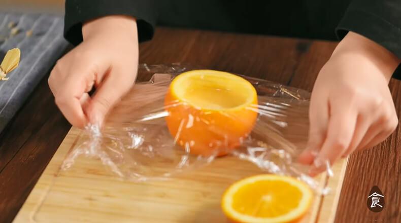 Wrap the oranges in plastic wrap